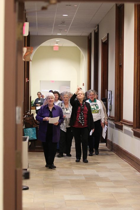 Retreat leader and Providence Associate Diann Neu and Providence Associate Sandra Hartlieb lead the retreatants on a pilgrimage walk through the halls of Providence Hall to the shrine of Saint Mother Theodore Guerin for the Saturday evening vigil.